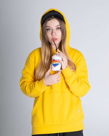 Young LGBTQ sad woman wearing yellow hoodie jacket holding a cup with rainbow heart, on gray background