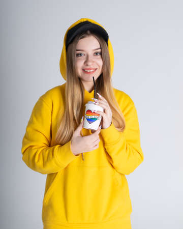 Young LGBTQ woman smiling broadly wearing yellow hoodie jacket holding a cup with rainbow heart.