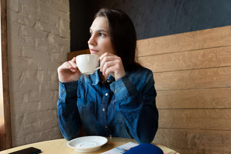 A girl in a blue denim shirt sits in a cafe and looks out the window, in the hands of a white mug with green tea