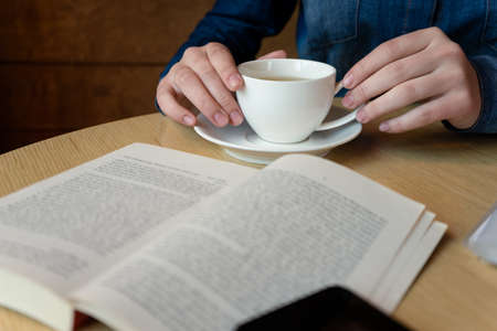 hands holding a white glass with green tea, in the foreground lies a book outside the sharpness zone, close up