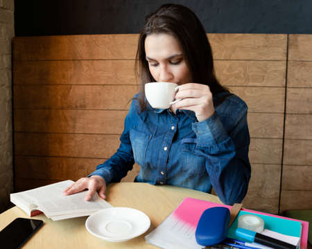 a thoughtful girl in a blue denim shirt sits in a cafe reading a book and drinking green tea in a white mug