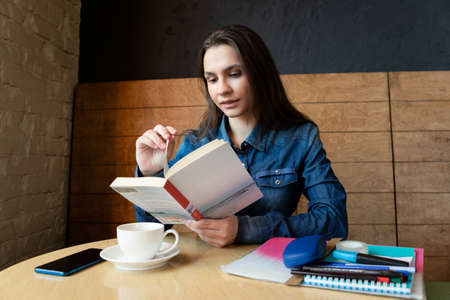A thoughtful girl in a blue denim shirt sits in a cafe and reads a book, there is tea green in a white mug