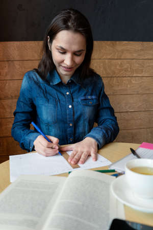 a cheerful girl draws a emotions schedule with a blue felt-tip pen using a wooden ruler, in front there is a book and a white mug with green tea