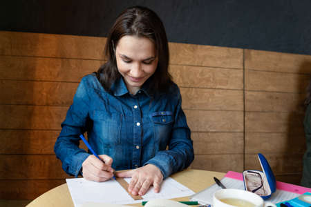 a cheerful girl draws a emotions schedule with a blue felt-tip pen using a wooden ruler, in front there is a book and a white mug with green tea Stock fotó