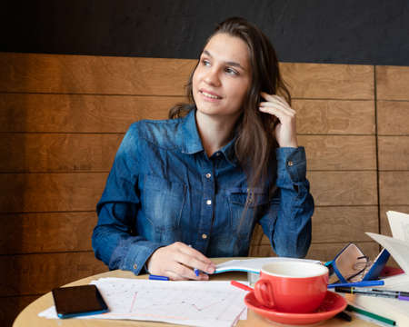 A cheerful girl in a blue denim shirt sitting in a cafe makes notes in a notepad with a pen. On the table sheets of paper, eyeglasses in a case, adhesive tape, felt-tip pens, a book, and a red mug