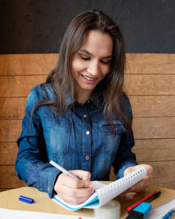 A cheerful girl in a blue denim shirt sitting in a cafe makes notes in a notepad with a pen. Sheets with various schedules, adhesive tape, a red mug with green tea, felt-tip pens are on the table Standard-Bild