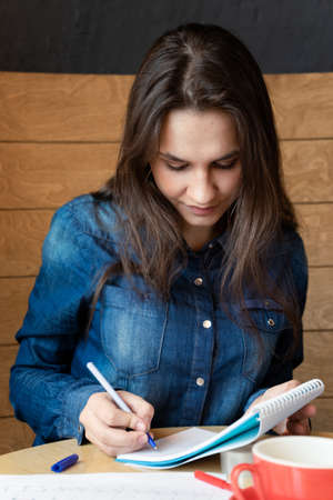 A serious girl in a blue denim shirt sitting in a cafe makes notes in a notepad with a pen. On the table sheets of paper, adhesive tape, and a red mug