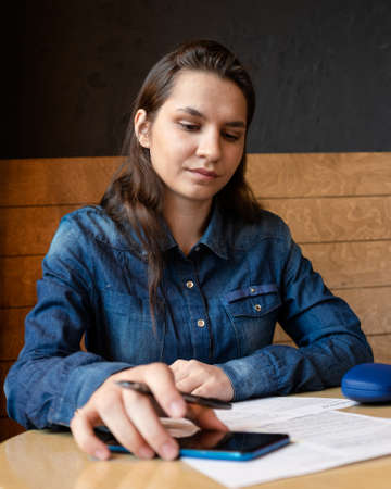 serious girl model signs the release, consults the sample moving a blue smartphone, woman in a denim shirt
