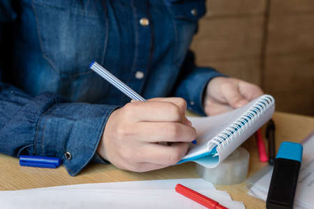 Girl in a blue denim shirt sitting in a cafe makes notes in a notepad with a pen. A sheets with various charts, adhesive tape, felt-tip pens are on the table. Close up