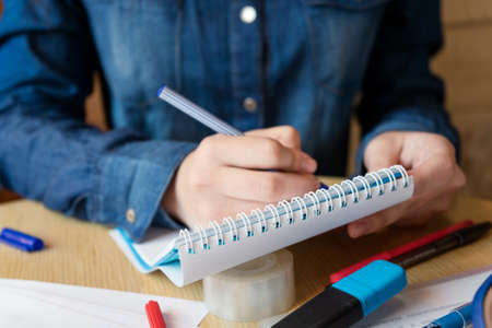 Girl in a blue denim shirt sitting in a cafe makes notes in a notepad with a pen. A sheets with various charts, adhesive tape, felt-tip pens are on the table. Close up Standard-Bild
