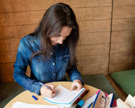 A serious girl in a blue denim shirt sitting in a cafe makes notes in a notepad with a pen. On the table sheets of paper, eyeglasses in a case, adhesive tape, felt-tip pens