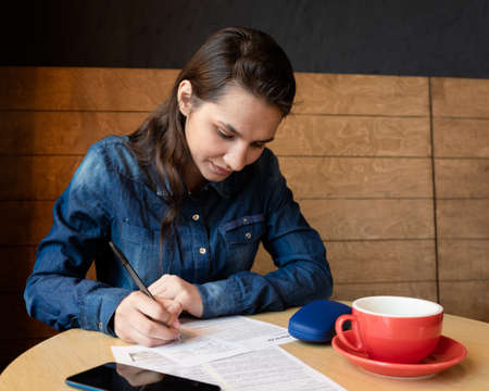 Serious girl model signs the release, there is a red mug on the table, blue glasses case and a smartphone, a woman in a denim shirt