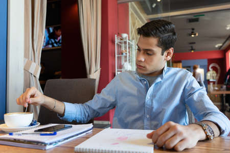 After signing an important contract, a young businessman wants to drink delicious coffee. In front of him are notepads, a pen, and a telephone. He's wearing a blue denim shirt and a nice watch Stock fotó
