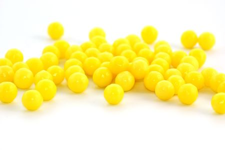 Many yellow pills on white