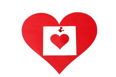 White note paper on red heart on white background