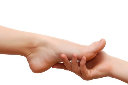 Mans hand keeps womans feet on the white background
