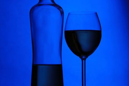 Wine glass and half-empty bottle on blue background