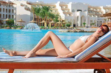 lounging: Beautiful woman sunbathing near the swimming pool