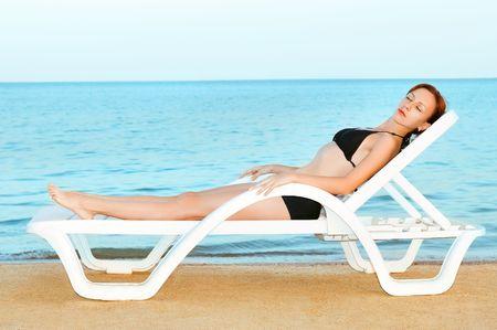 Beautiful woman sunbathing on the sea beach