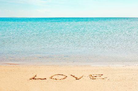 Love word written on the beach near the sea