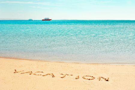 Vacation word written on the beach near the sea