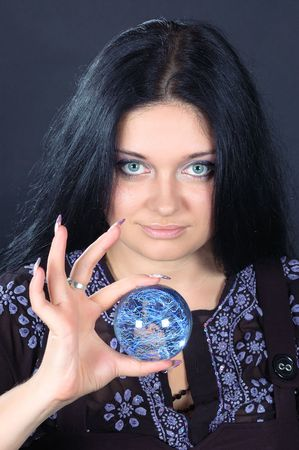 diviner: Beautifu smiling black-haired witch holding the magic sphere Stock Photo
