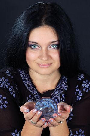Beautiful black-haired witch holding the magic sphere in both hands photo