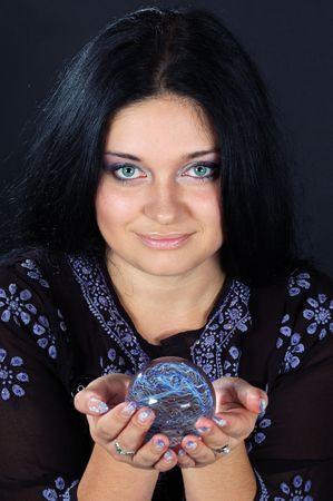 pr�voyance: Belle sorci�re aux cheveux noire contenant la sph�re magique � deux mains