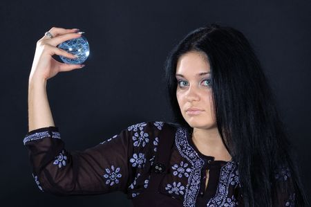 Beautifu black-haired witch holding the magic sphere in one hand Stock Photo - 6133981