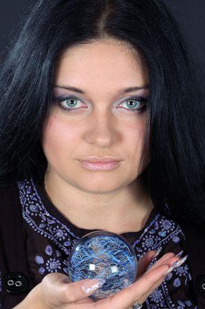 pr�voyance: Belle sorci�re aux cheveux noire souriant d�tenant la sph�re magique  Banque d'images