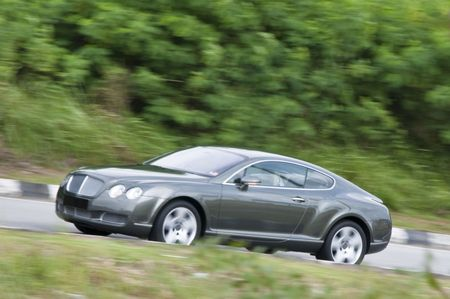 panning shot: Un colpo di panning di una vettura grigio brunastro su strada con sfondo sfocato