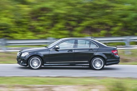 panning: A panning shot of black car on the road with blurred background