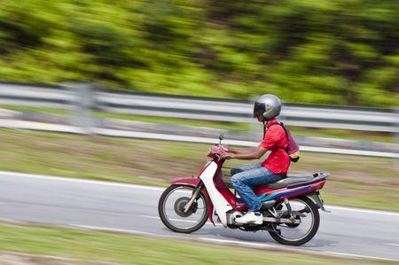 panning shot: Colpo di un motociclista su una moto con sfondo sfocata di panning