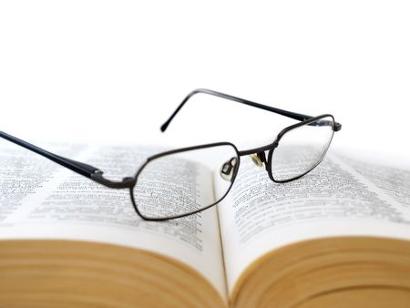 Closeup of opened book with glasses on it, on white background,shallow DOF,focus on glasses