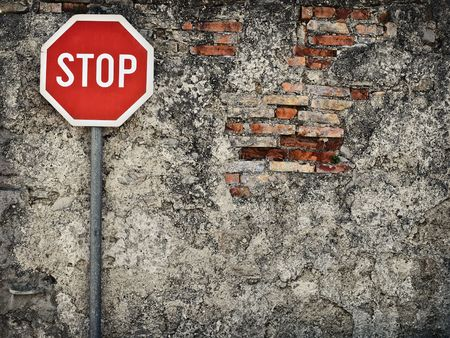 unkempt: stop sign against grungy wall, may represent protection,dead end,wrong way,resistance...