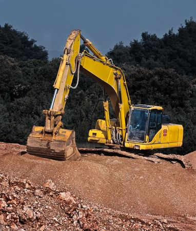positioned: excavator positioned on the gravel piled-up workplace Stock Photo