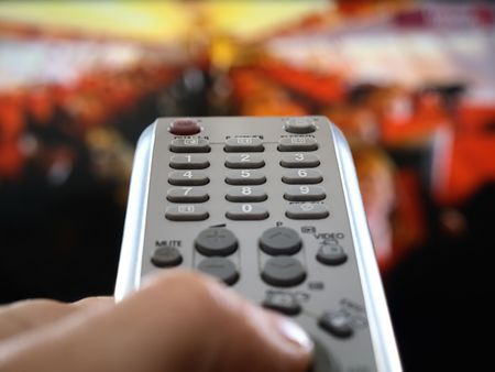 closup of a hand  holding the remote control infront of the television, shallow DOF, conceptual image of the world under control
