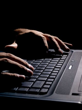 security search: male hands on the keyboard,low key and high contrast,may suggest cyber crime, hacking,spying