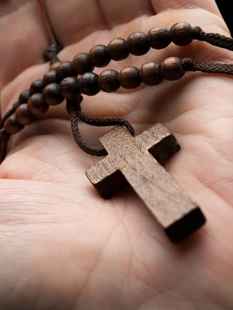rosary in the hand with focus on the cross, shallow DOF photo