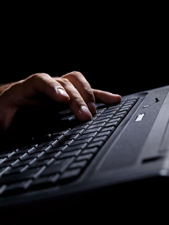 closeup of a man's hand on a keyboard in a low light environment, may be used for various internet related topics, focus on may be used for various internet related topics, focus on the man's fingers , high contrast and shallow DOF