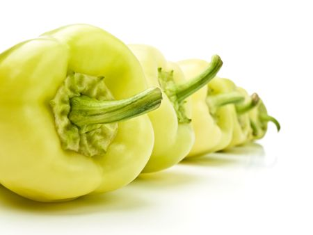 yellow-green bell peppers in a row, against white background, shallow DOF