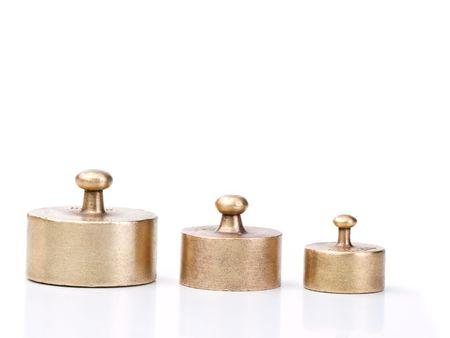 balanza en equilibrio: tres antiguos y equilibrio gastada escalar�n pesos en distintos tama�os, sobre fondo blanco  Foto de archivo