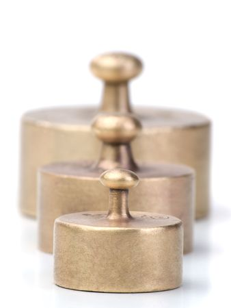 three older and worn-out  balance scale weights in different sizes , against white background, shallow DOF