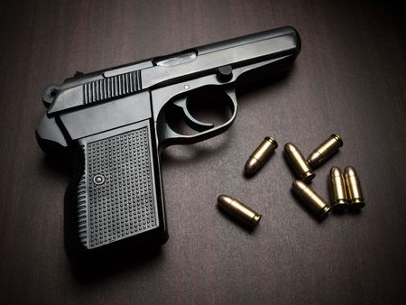 gun barrel: handgun with bullets on the wooden surface, closeup with vignette, useful for various security,protection or criminal topics