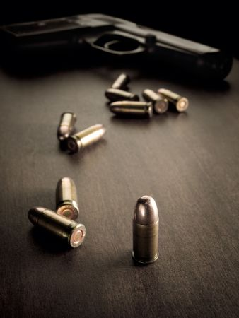 the topics:  bullets with handgun in the back of the scene with focus on the bullet,sepia toned, closeup with vignette, useful for various security,protection or criminal topics Stock Photo