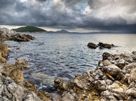 rocky shore on the Adriatic sea with the rainy clouds , HDR image