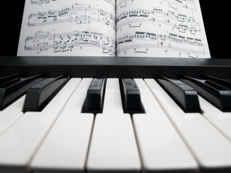piano and the note sheets, focus on the black keys with notes reflection photo