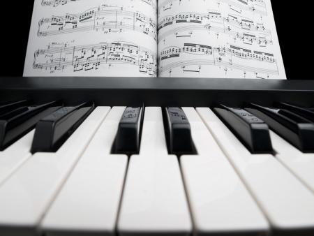 piano y las hojas de la nota, se centrará en las teclas negras con notas de reflexión Foto de archivo - 6761743