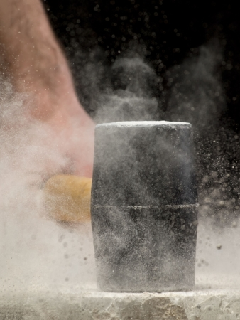 smash: man breaking the stone, may be used as concept for power,strength,destruction,fury,anger,resistance...closeup image with shallow DOF