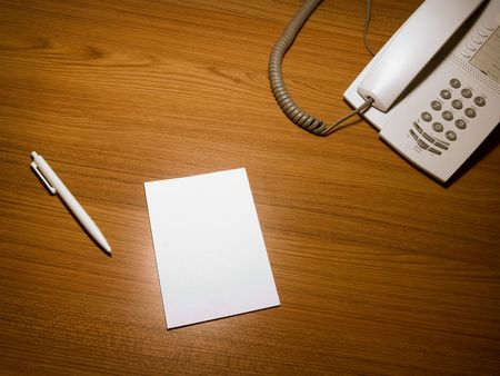 Blank white paper on the wooden working desk with the pen and telephone,shot taken from above Stock Photo